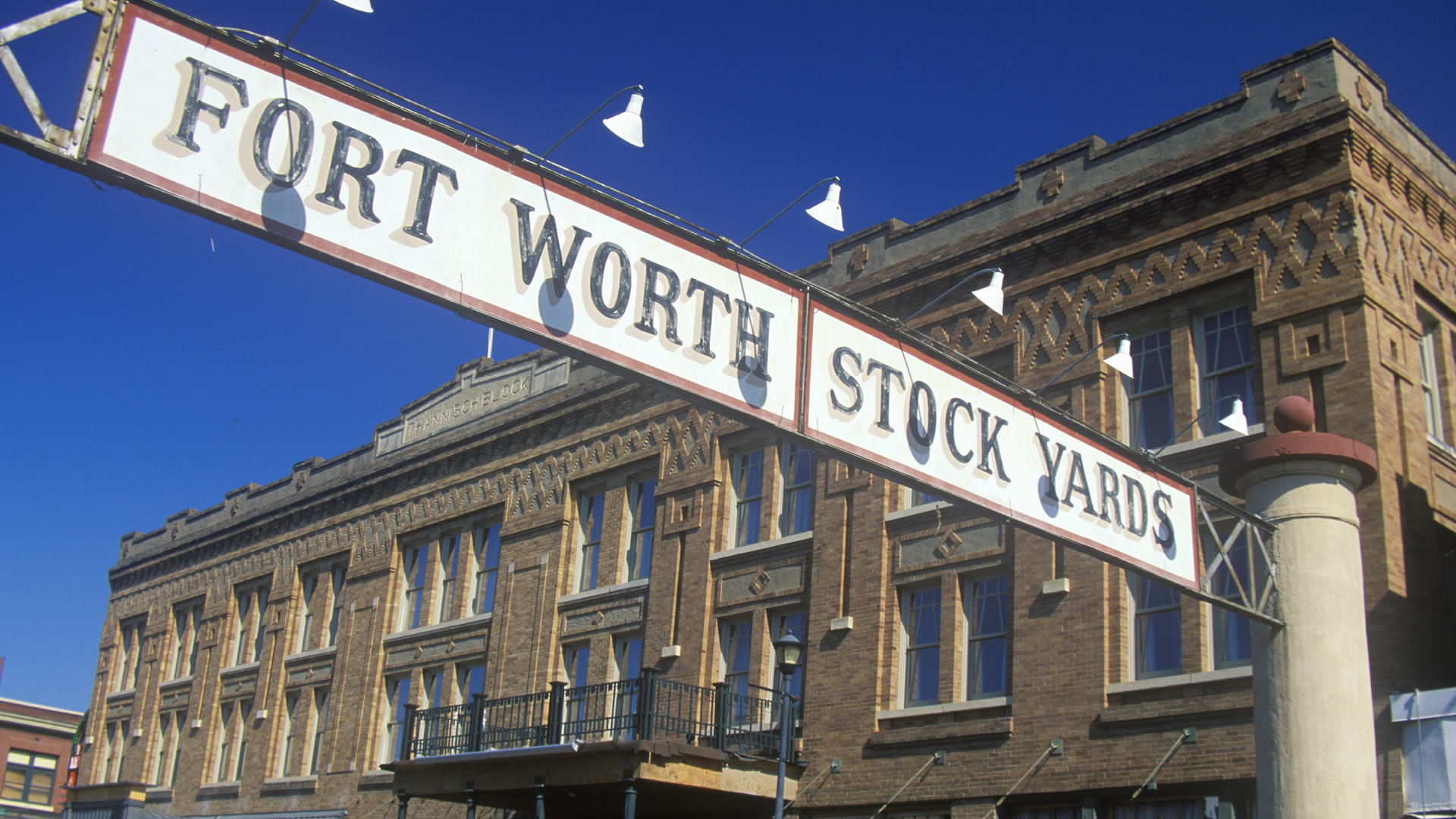 Banner at the Fort Worth Stockyards with historic hotel, Ft. Worth, TX
