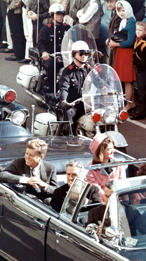 Picture of President Kennedy in the limousine in Dallas, Texas, on Main Street, minutes before the assassination. Also in the presidential limousine are Jackie Kennedy, Texas Governor John Connally, and his wife, Nellie.